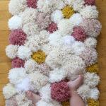 Alfombra para el bebe realizada con pompones de lana