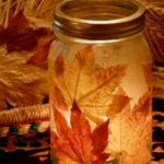 Centros de mesa confeccionados con frascos de vidrio decorados con hojas de otoño
